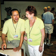 Claire Mather and Nelson Rodriguez view Claire's summer photographs while other DIGS members socialize before the meeting begins; photographer: Bill Brennan