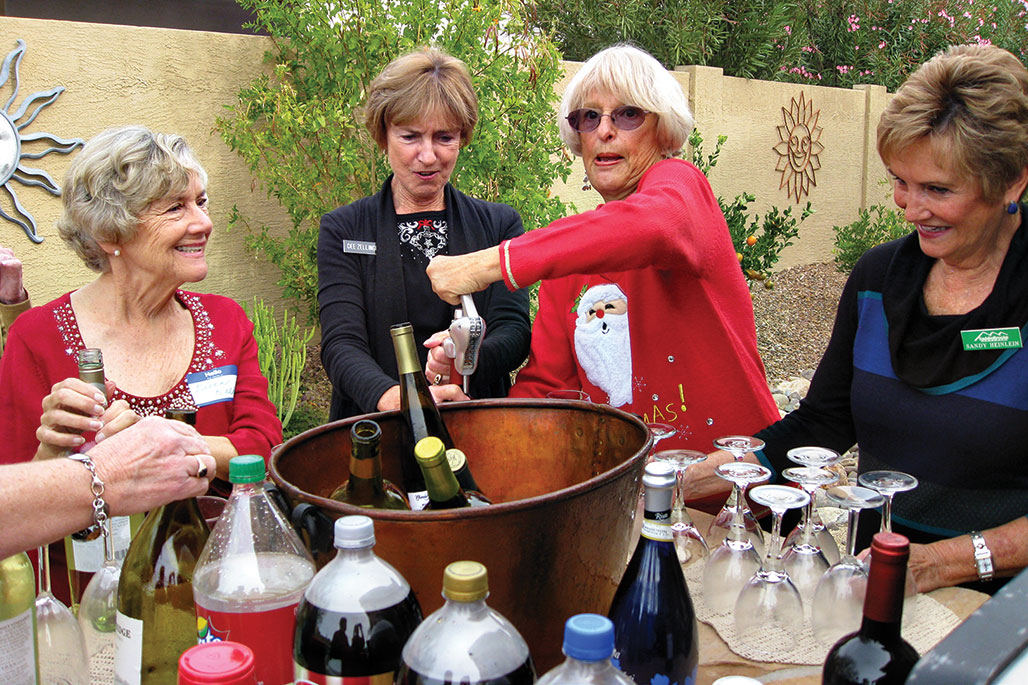 Eileen Halk (left) and Sandy Heinlein (right) watch Dee Zellinger and Sybil Byrnes pull a cork from a bottle of wine at the Unit 21 Women's Holiday Luncheon.