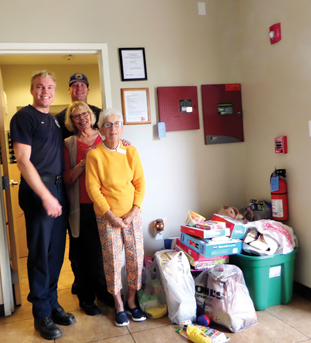 Willie Reich and Helen Nack deliver toys to SaddleBrooke firemen.