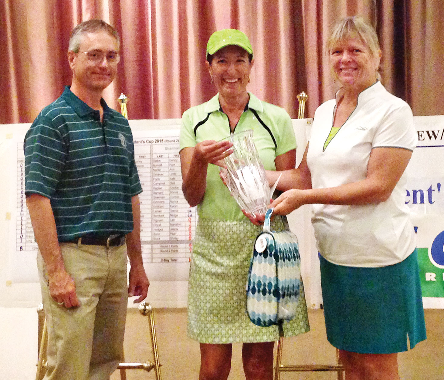 Pilar Borm accepts trophy from 2014 winner Donna Barnard, with Pro Mike Jahaske.
