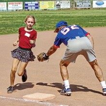 This young lady avoids the tag from Coach Q and she is safe at third base! Photo by Jim Smith.