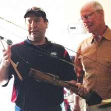 Bobby Vargas from PSE Marketing Department shows Ed Snyder some features of a compound bow.