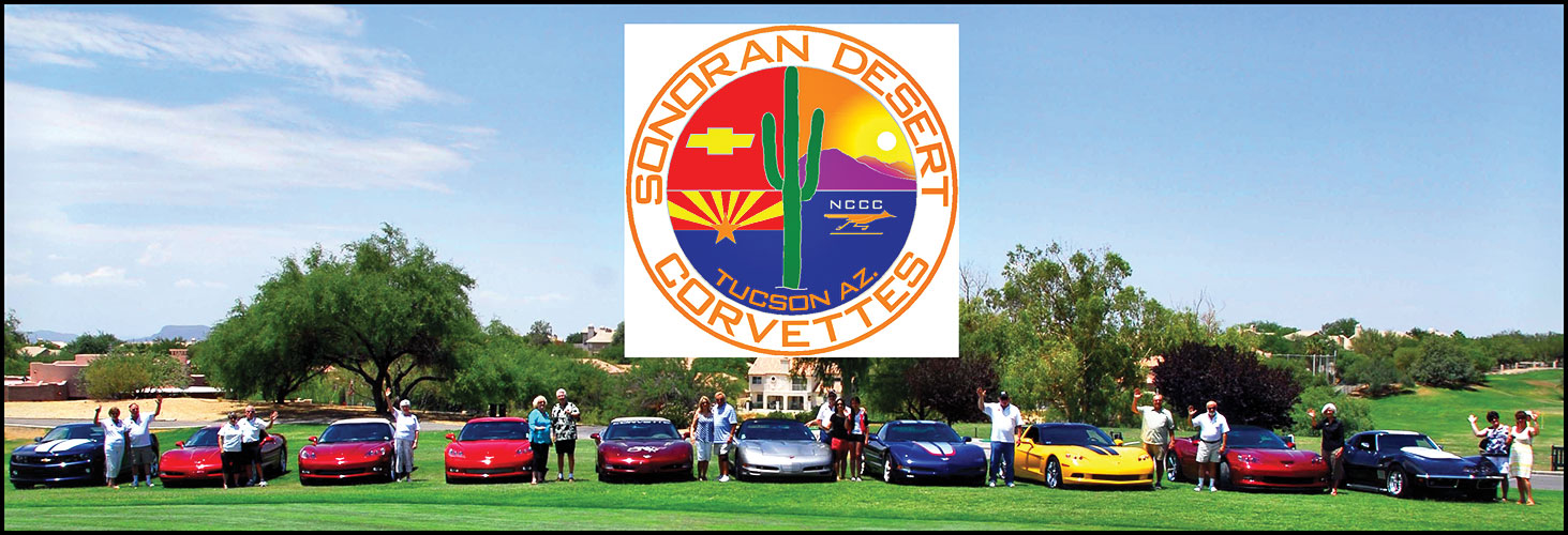 Club members gather at the Vette logo sign.