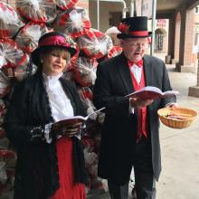 Leah and Ron Kari dressed as Charles Dickens era carolers.