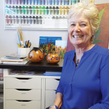 Nancy Springer sits in her studio with two newly completed gourds.