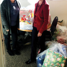 Carol Bowman (right) delivers Christmas presents to Brenda Garcia in the Impact office.