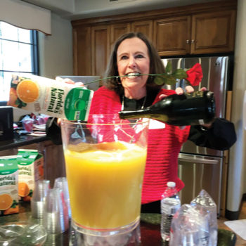 Social Committee member Maureen Spence prepares a pitcher of mimosas for guests at the Villas 2 Valentine Brunch.