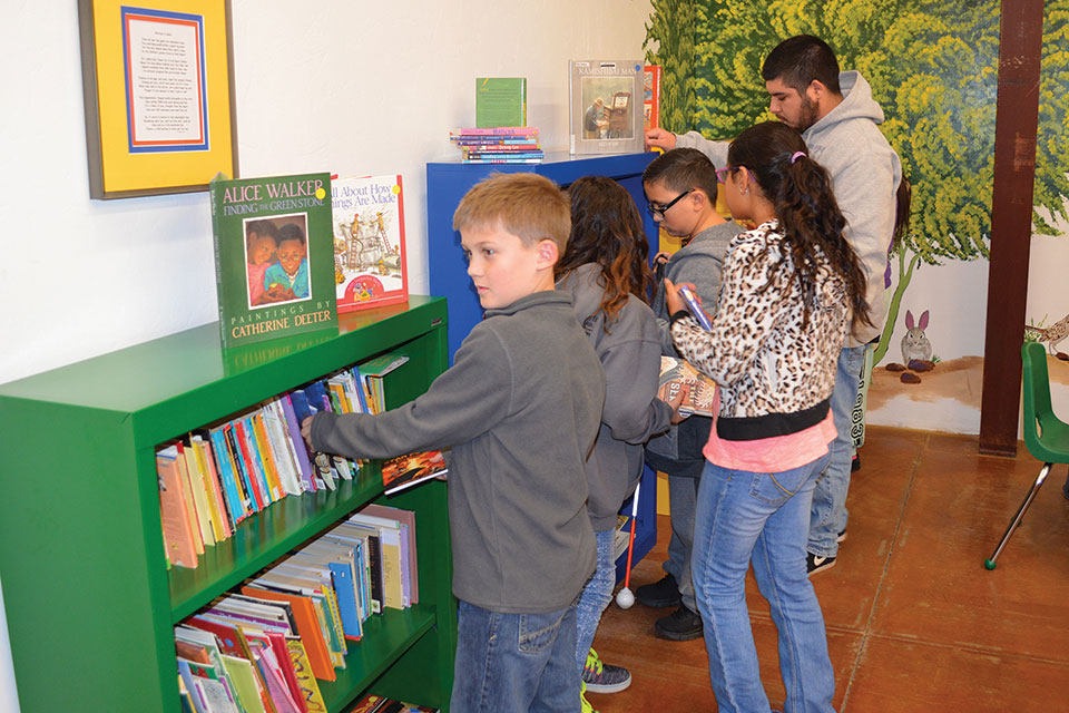 Kids at the Closet select books to take home.
