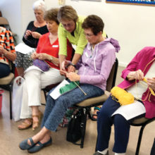Pat Lenz offers assistance to her students in the Portuguese knitting class; photo by Georgiann Schwetz.