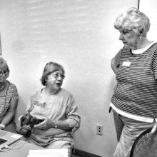 Jeannie Hayward, Barbara Wilder and JoAnn Koblewski talking about cameras; photo by Bill Grinonneau