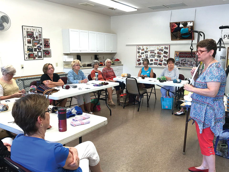 Tina Marie leads the group in learning how to make fingerless gloves.