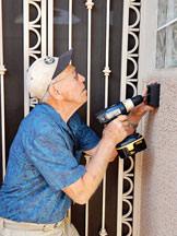 Chuck Sanden, a Senior Village volunteer, works on installing a Golder Ranch Fire Department lockbox for emergency responders.