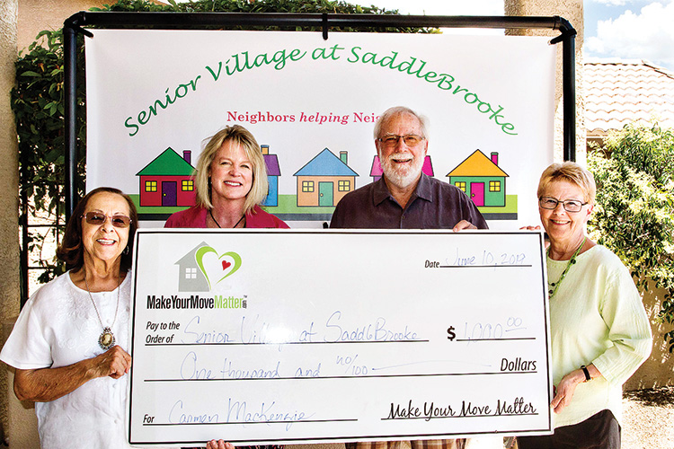 Realty Executives agent Beth Fedor (second from left) and her associate Jo Parsons (right) present a donation check to David Loendorf, Senior Village president, on behalf of their client Carmen Mackenzie (left).