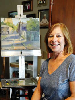 Janet Tucker pauses in her studio with an in-progress work.