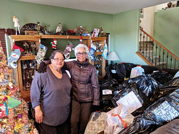 Carmen Whirley, liaison and gift coordinator for children of the military, and Bonnie Barazani, buried in bags of holiday gifts
