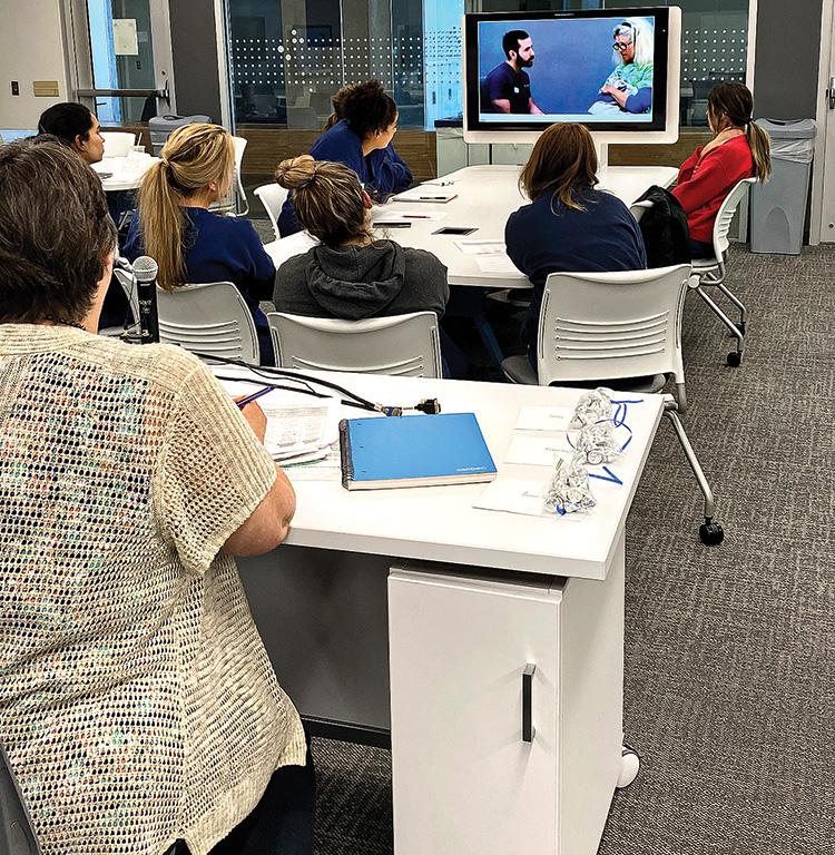 Susan Schweitzer being interviewed on television while student nurses watch.