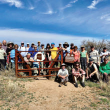 Trail workers pose before a trail gate. Photo by Zach MacDonald.