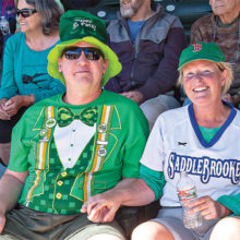 Jason Noffsinger and Sue O'Donnell enjoy the action at SaddleBrooke Senior Softball's annual St. Patrick's Day Tournament. (Photo by Dennis Purcell)