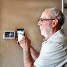 David Loendorf, Senior Village president, uses his cell phone to set the room temperature at home.