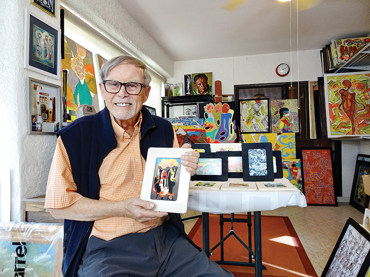Paul Kopp displays a miniature photograph from one of his original pieces in his painting-filled studio. (Photo by LaVerne Kyriss)