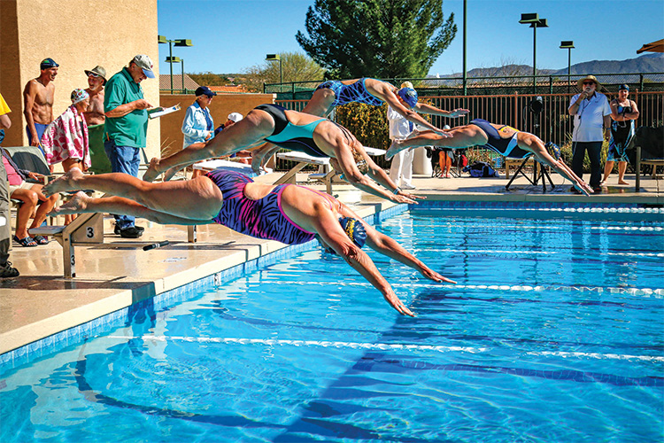 Swimmers from Willer's Killer Whales and Jim's Desert Sharks start off the blocks in an individual event.