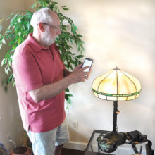 David Loendorf, president of Senior Village, adjusts his home lighting system to come on at dusk and turn off at a set hour via his cell phone.