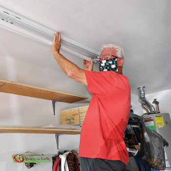 Terry Sterling, a volunteer on the Senior Village Helping Hands team, replaces a garage light for a Village member. This team offers many home and yard services, including computer consulting.