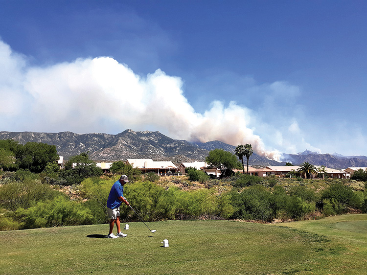 Golfers teeing off and playing with the smoke clouds and fire in the background (Photo by Fred Pilster)