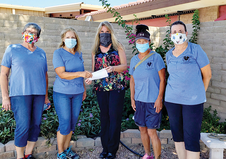 Audra Michael, director of Pinal County Animal Care and Control (center) accepts a check from Mera Laureys as Friends of Pinal County Animal Shelter & Rescues, Inc. volunteers Julie Furgason (far left), Alice Link Lopez, and Kathi Ryzska look on.