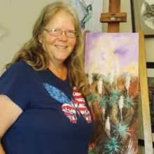 Delys Nast smiles in her studio with an in-progress painting. (Photo by LaVerne Kyriss)