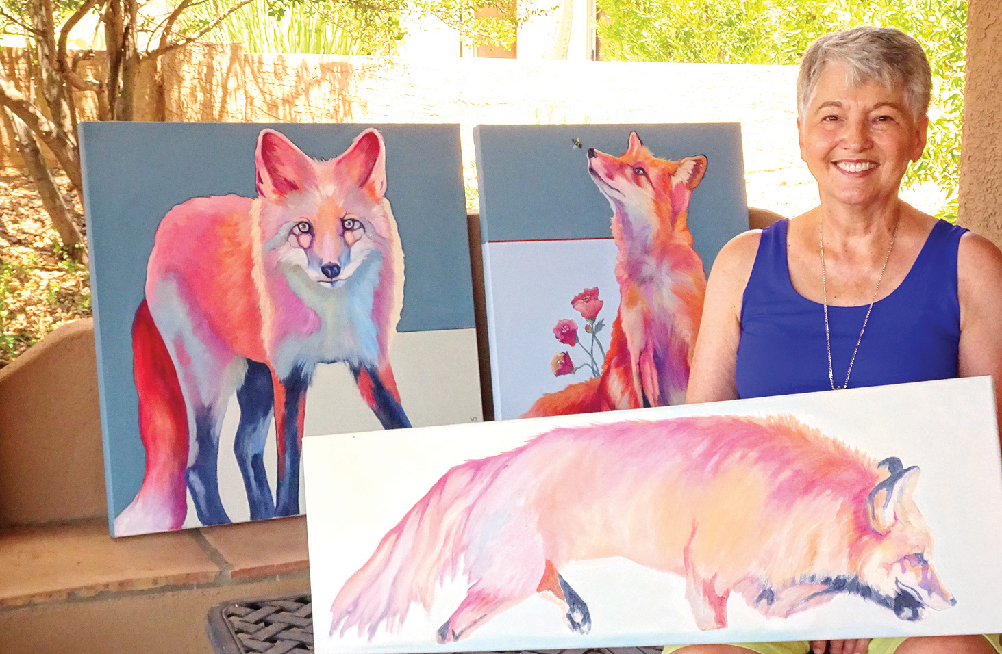 Rose Collins holds an in-progress work in her newest series. Behind her are two more paintings in this series, Foxy Lady (left) and Peaches meets Buzz. (Photo by LaVerne Kyriss)