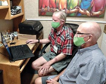 Volunteer Bill Lunquist helping Village member Bill Smith install a new computer and printer