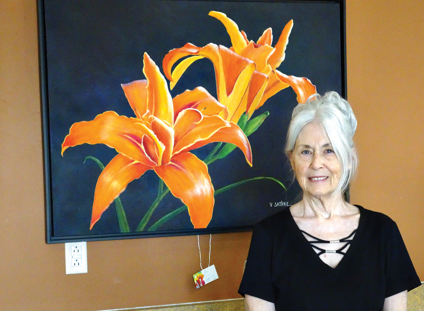 """Vivian Sathre shows off """"Double Lilies,"""" one of her large floral paintings done in an acrylic medium. (Photo by LaVerne Kyriss)"""