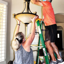 Senior Village volunteer Greg Nelson raises a lamp with an assist from Jean Romine's daughter Krys.