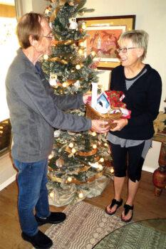 Senior Village volunteer Tom Borkovec presents member Elizabeth Conti with a surprise holiday gift basket.