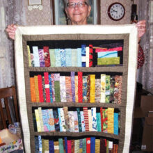 "Ellen Wixom's sister Nancy with the ""library"" quilt Ellen made for her. The books in the quilt reflect Nancy's lifelong passions and interests."
