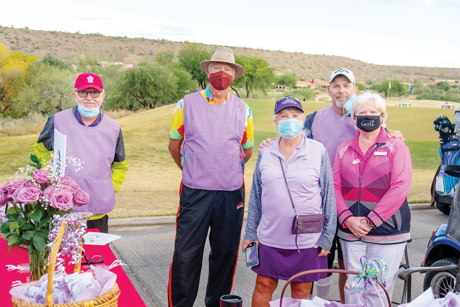 Larry McNamee, admiring the check-in table and gift bags prepared by wife, Loralee; Dan Nordhill; Event Chair, Loralee Horwedel; Matt Kambic; and Barbara Bloch, dressed in plum to honor cancer caregivers. (Photo by Bill George)