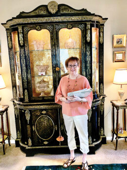 Sandi Newberry with a French Boulle Breakfront cabinet, Louis XIV style, circa 1850 with brass marquetry work and gilt-bronze mounts. Andre Boulle was the head cabinetmaker for King Louis XIV. Some Boulle original pieces of furniture were made around 1700 and can be seen at the Louvre Museum in Paris. During the last half of the 19th century, modern machine techniques were utilized to create large quantities of furniture made in the Boulle style with inlaid brass and bronze work on ebonized wood.
