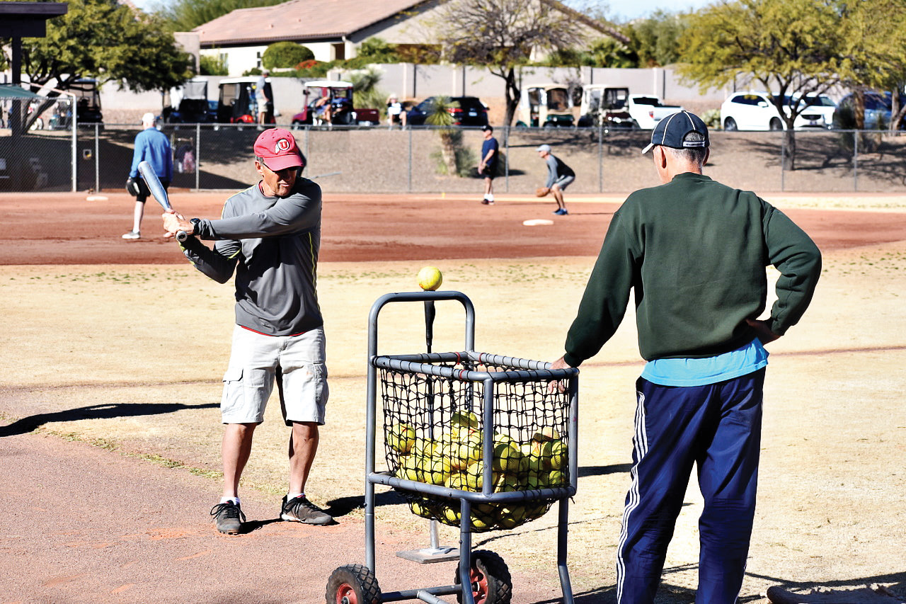 Skills Clinic Commissioner Peter Romeo watches Wayne Stafford practice his swing off the batting tee.