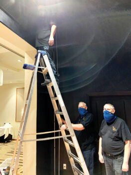 Left to right: Frank Calsbeek and his son, Frankie, assist Joey Mendoza (on ladder) with hanging the main curtain. (Photo by Shawne Cryderman)