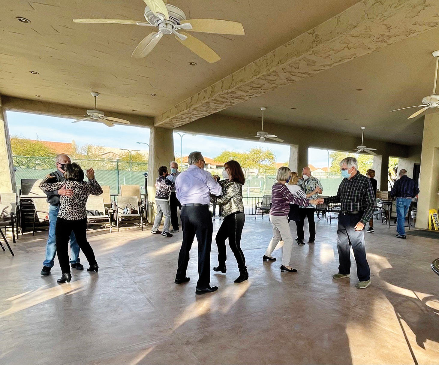 Dancing at the tennis pavilion—outdoors, socially distanced, and with masks.