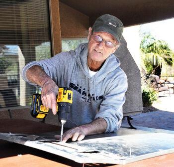 Senior Village volunteer Steve Wiley repairs a panel for a member's spa.