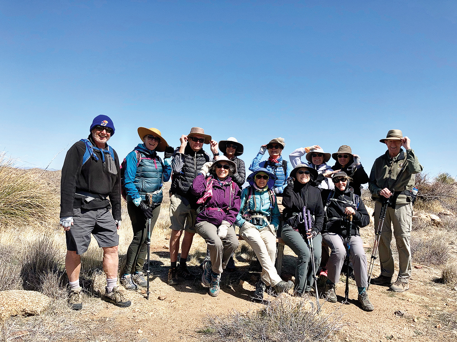 Hikers hold their hats at the Wildlife Corridor Bench (Photo by Lynda Green)